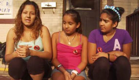 3 young sisters sitting on front porch talking to camera