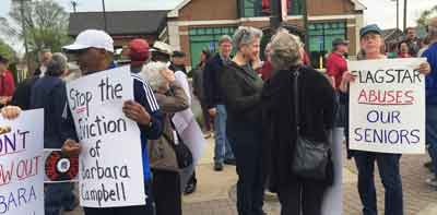 People in front of bank with signs: Stop the Eviction  of Barbara Campbell & Flagstar Abuses our Seniors